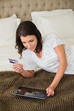 Calm pretty brown haired woman shopping online with her tablet pc