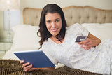 Cheerful pretty brown haired woman shopping online with her tablet pc