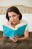 Pensive pretty brown haired woman reading a book