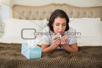 Casual pretty brown haired woman sneezing in a tissue