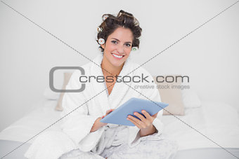 Smiling natural brunette using tablet