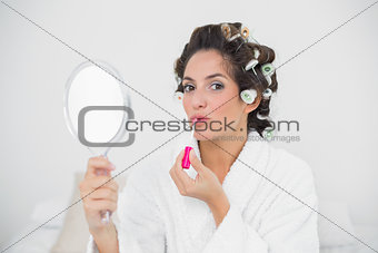 Calm natural brunette putting lip gloss on