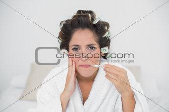 Grimacing natural brunette holding thermometer