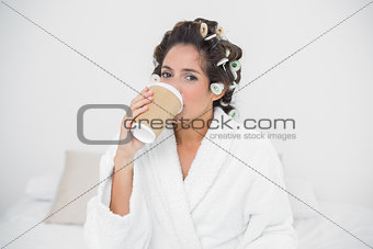 Calm natural brunette drinking from disposable cup
