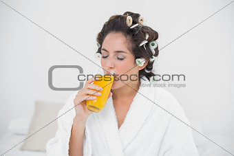 Calm natural brunette drinking glass of orange juice