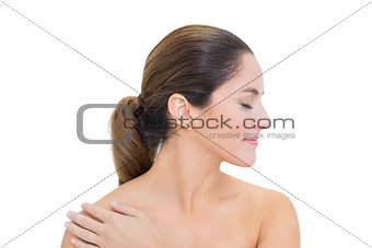 Smiling bare brunette turning head right with closed eyes