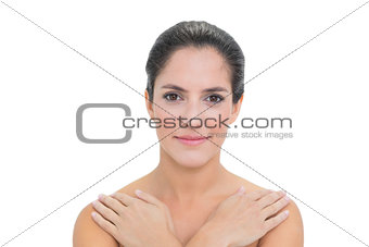 Smiling bare brunette touching both shoulders