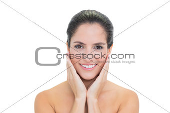 Smiling bare brunette touching her face