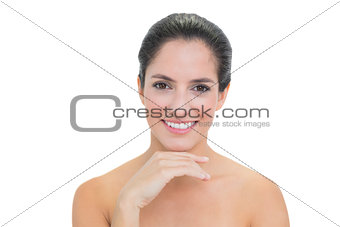 Smiling bare brunette touching her chin