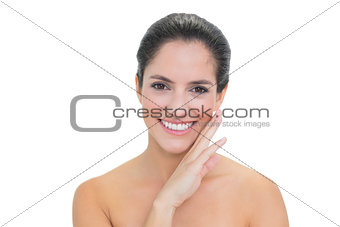 Smiling bare brunette touching her right cheek
