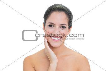 Smiling bare brunette touching her left cheek