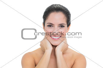 Smiling bare brunette touching her neck with both hands