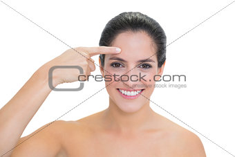 Smiling bare brunette pointing at forehead