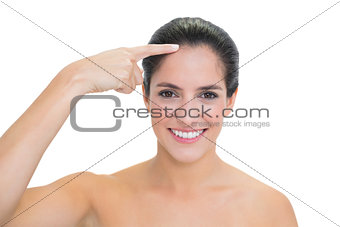 Smiling bare brunette touching forehead