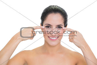 Smiling bare brunette pointing at both her eyes