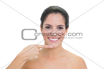 Smiling bare brunette pointing at her chin