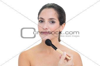Calm bare brunette holding powder brush