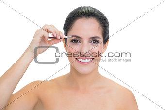 Smiling bare brunette using tweezers