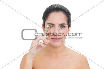 Calm bare brunette using eyelash curler
