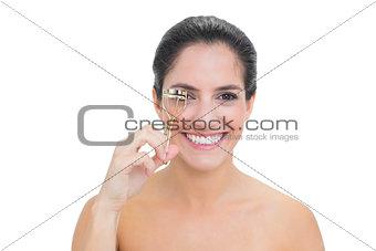 Smiling bare brunette using eyelash curler