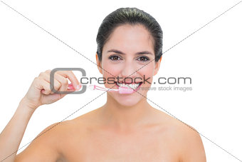 Smiling bare brunette using toothbrush