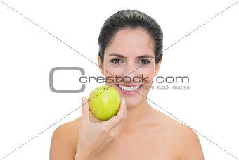Smiling bare brunette holding green apple