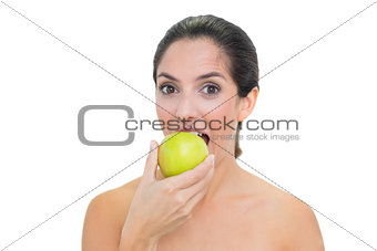 Smiling bare brunette eating green apple