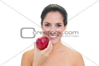 Smiling bare brunette holding red apple