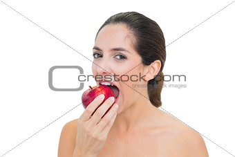Smiling bare brunette eating red apple