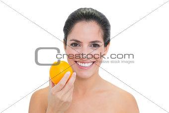 Smiling bare brunette holding orange