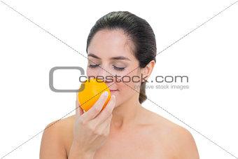 Smiling bare brunette smelling an orange