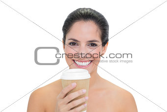 Smiling bare brunette holding disposable cup