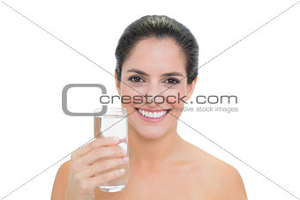 Smiling bare brunette holding glass of water