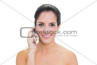 Smiling bare brunette phoning
