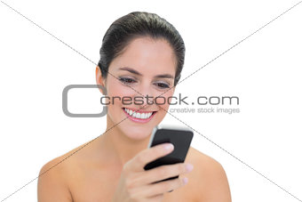 Smiling bare brunette using smartphone