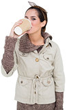 Content cute brunette in winter fashion drinking from disposable cup