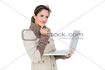 Thoughtful cute brunette in winter fashion using laptop