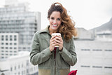 Smiling gorgeous brunette in winter fashion holding disposable cup