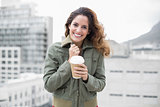 Cheerful gorgeous brunette in winter fashion holding disposable cup