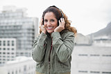 Happy gorgeous brunette in winter fashion listening to music