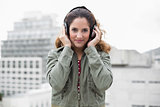 Content gorgeous brunette in winter fashion listening to music
