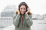 Cheery smiling gorgeous brunette in winter fashion listening to music