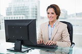 Cheerful businesswoman sitting in front of computer
