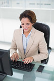 Cheerful businesswoman looking at keyboard