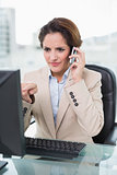 Businesswoman pointing at computer on a phone call