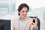 Furious businesswoman shouting at smartphone