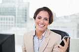 Cheerful businesswoman holding smartphone