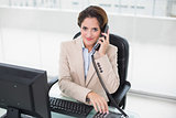 Brunette businesswoman using phone and smiling at camera