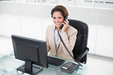 Brunette businesswoman using phone and looking at camera