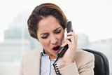 Outraged businesswoman shouting into phone